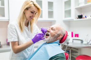 The dentist carefully places the fake tooth the patient's mouth.