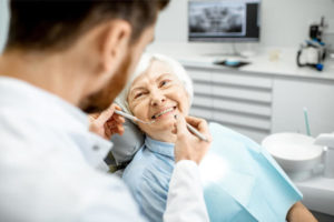 The senior patient smiles first at her dentist before the procedure begin.