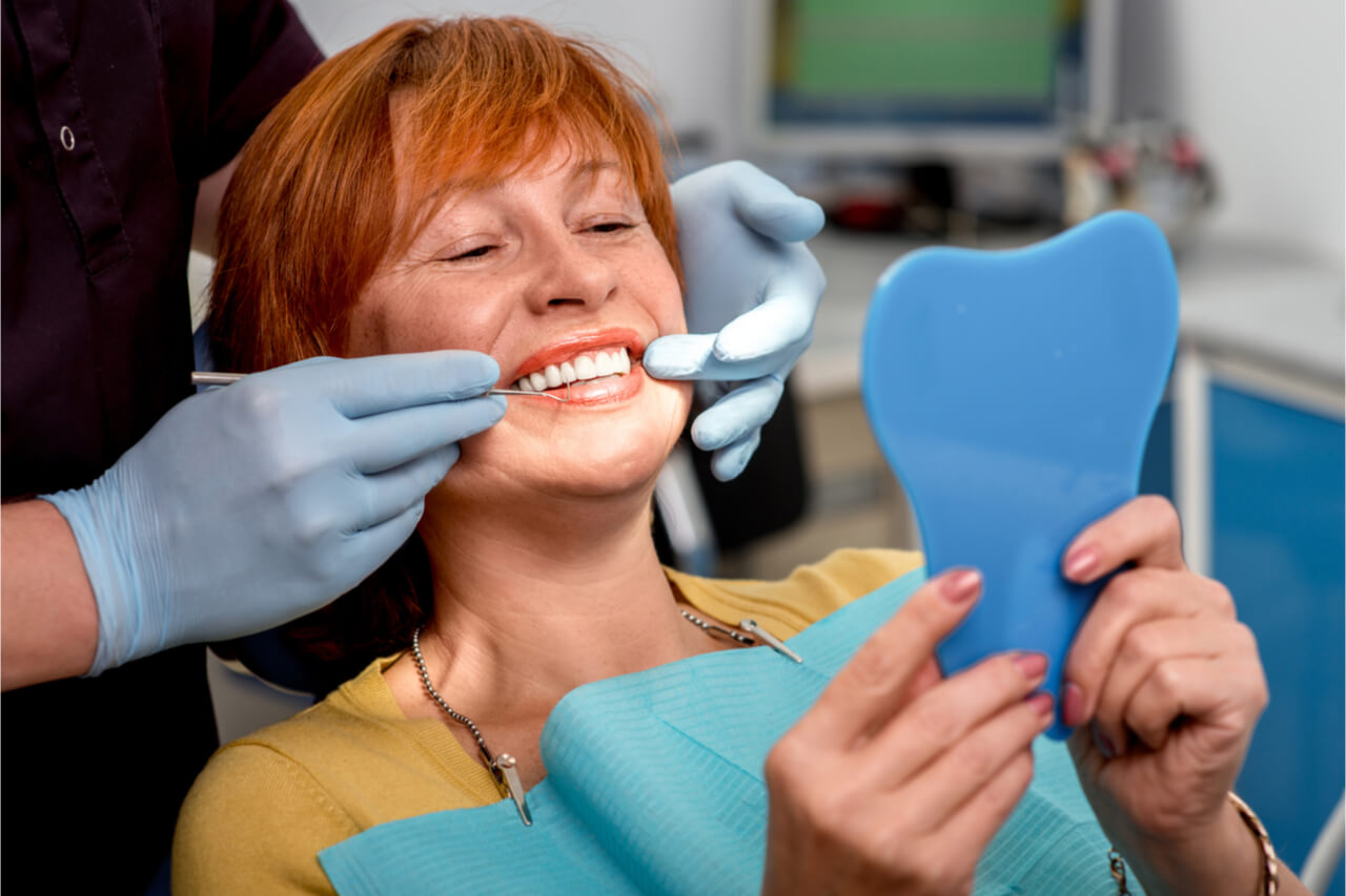 The patient looks at the mirror after the dental treatment.
